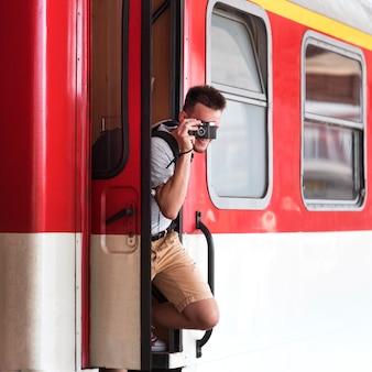 Mężczyzna robi zdjęcia z pociągu