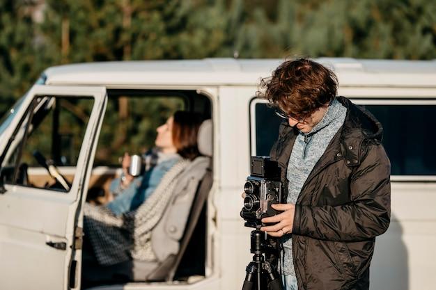 Mężczyzna robi zdjęcie aparatem retro obok swojej furgonetki
