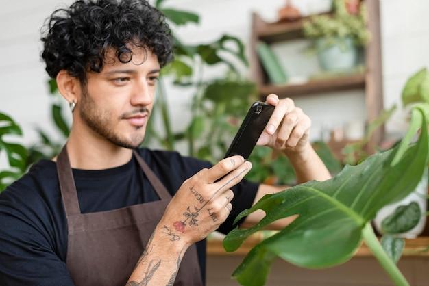 Mężczyzna robi zdjęcie rośliny doniczkowej, aby udostępnić ją w mediach społecznościowych