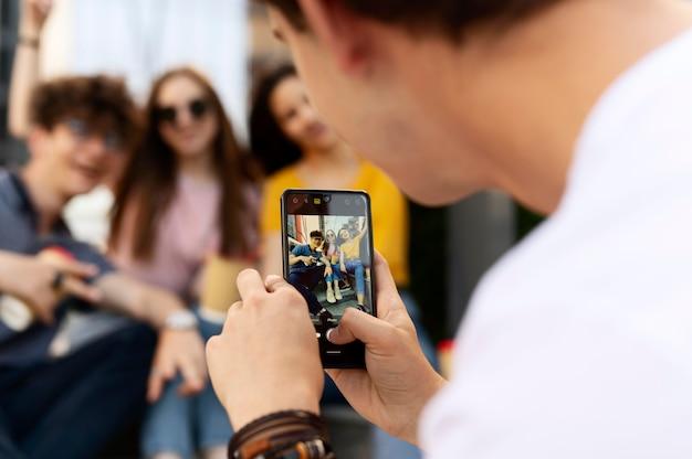Mężczyzna robi zdjęcie swoim przyjaciołom na zewnątrz