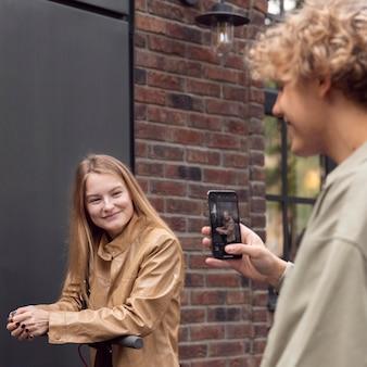 Mężczyzna robi zdjęcie swojej dziewczynie podczas jazdy na skuterze elektrycznym