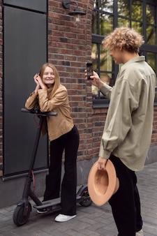 Mężczyzna robi zdjęcie swojej dziewczyny z hulajnogą elektryczną