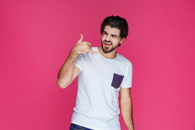 Mężczyzna robi znak wywoławczy gestami ręki.
