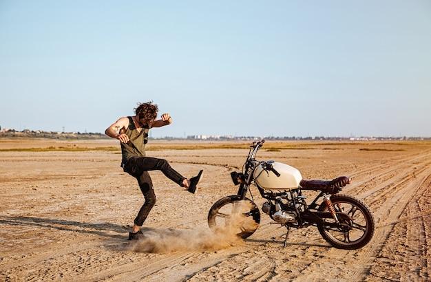 Mężczyzna robiący kurz stojący obok swojego motocykla na pustyni