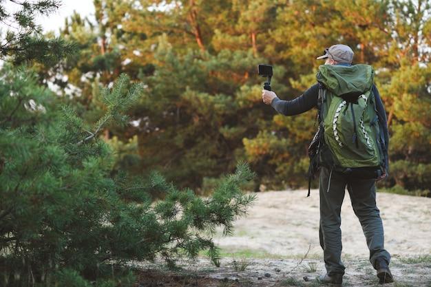 Mężczyzna robiący zdjęcia i filmy z pięknych miejsc ze stabilizatorem na telefon komórkowy