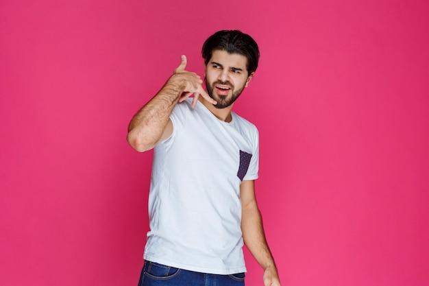 Mężczyzna robiący znak, który chce wkrótce usłyszeć od drugiej osoby.