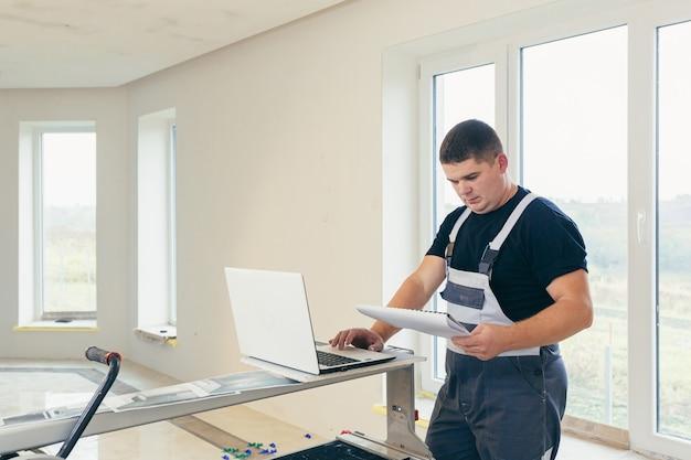 Mężczyzna robotnik budowlany patrząc na laptopa z projektem budowlanym