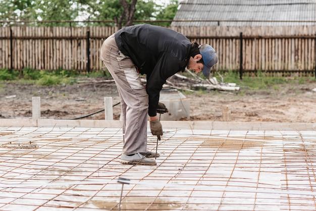 Mężczyzna robotnik budowlany przygotowuje pręt zbrojeniowy pod fundament budowy domu