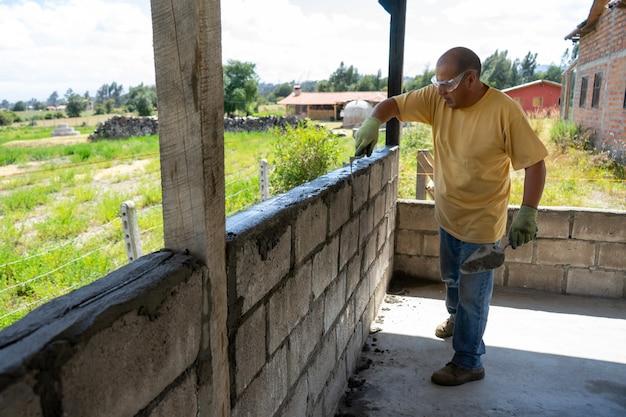 Mężczyzna robotnik budujący ścianę z bloków bryzy