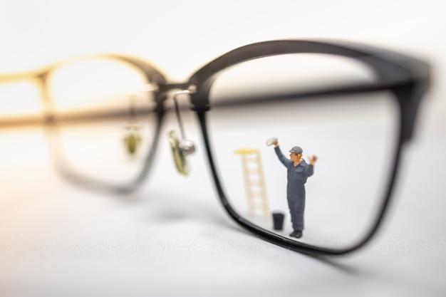 Mężczyzna robotnik miniaturowy rysunek wytrzeć i oczyścić brudne okulary do czytania z wiadrem i drabiną na białym stole.