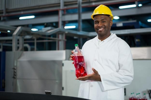 Mężczyzna robotnik pokazuje butelkę soku w fabryce