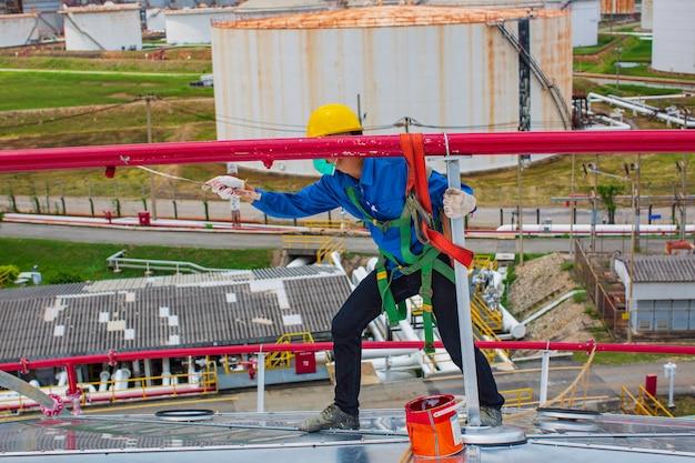 Mężczyzna robotnik pomalowany na czerwono na dachu zbiornika wody przeciwpożarowej rurociągu.