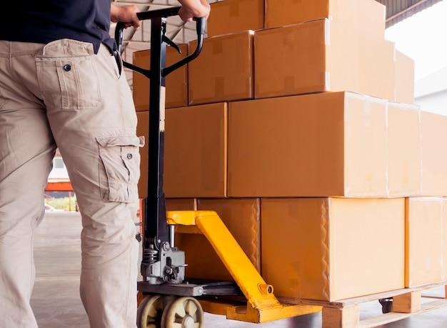 Mężczyzna robotnik rozładunku pudła przesyłki na palecie z ręcznym wózkiem paletowym