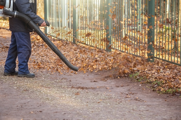 Mężczyzna robotnik usuwa trawnik dmuchawy do liści z jesiennego ogrodu.