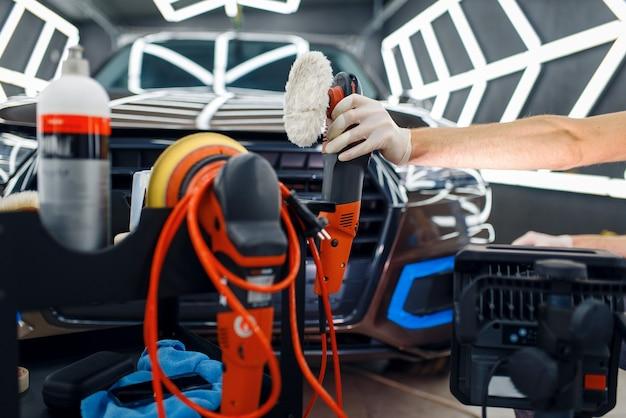 Mężczyzna robotnik w pobliżu skrzynki narzędziowej z maszyną do polerowania i narzędziami do polerowania, detalowanie samochodu. przygotowanie przed montażem powłoki chroniącej lakier samochodu przed zarysowaniami, auto tuning