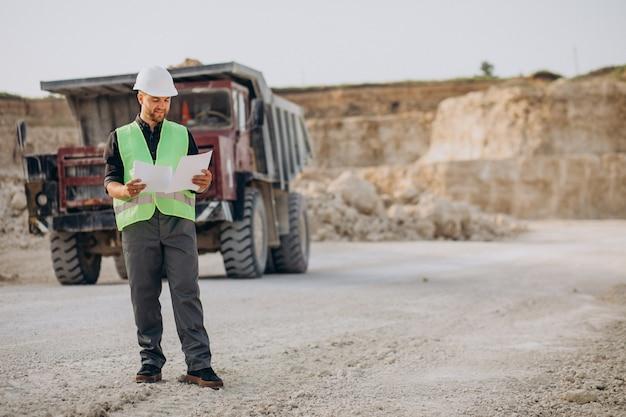 Mężczyzna robotnik z buldożerem w kamieniołomie piasku
