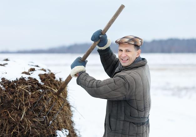 Mężczyzna rolnik pracuje z obornikiem wczesną wiosną