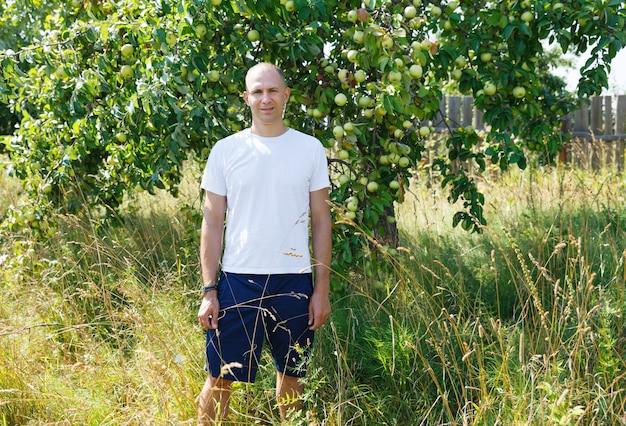 Mężczyzna rolnik w ogrodzie jabłoni