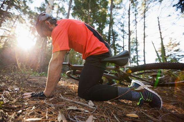 Mężczyzna rowerzysta górski spadł z roweru w lesie
