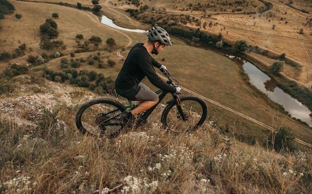 Mężczyzna rowerzysta jedzie na rowerze górskim na zboczu wzgórza
