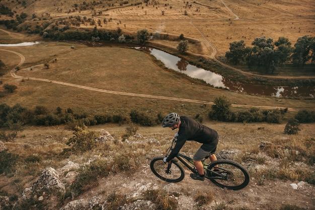 Mężczyzna rowerzysta jedzie na rowerze na wyboistej ścieżce