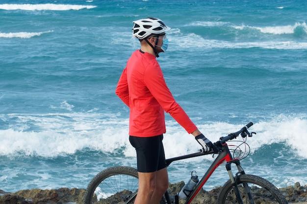 Mężczyzna rowerzysta nosi maskę ochronną i stoi na brzegu oceanu z rowerem górskim