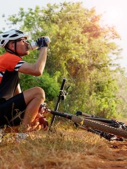 Mężczyzna rowerzysta siedzi w pobliżu rower pije wodę