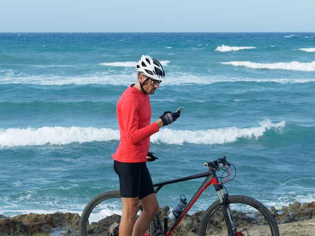 Mężczyzna rowerzysta stoi na brzegu oceanu z rowerem górskim patrząc na telefon