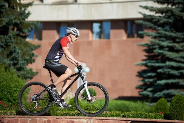 Mężczyzna rowerzysta szkolenia na obrzeżach ulicy