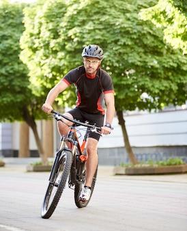 Mężczyzna rowerzysta szkolenia w centrum miasta