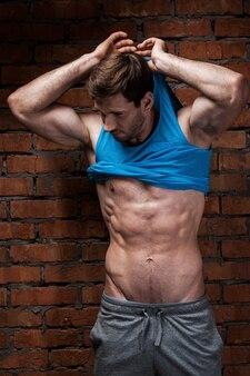 Mężczyzna rozbiera się. przystojny młody muskularny mężczyzna zdejmujący swój podkoszulek