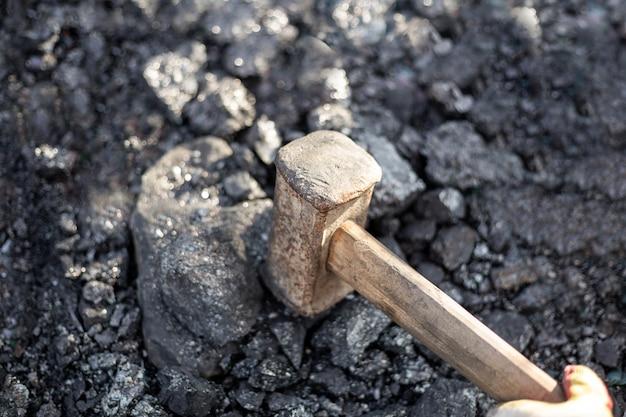 Mężczyzna rozbija młotem kowalskim mineralne paliwo stałe do pieców i kominków . duże kawałki węgla