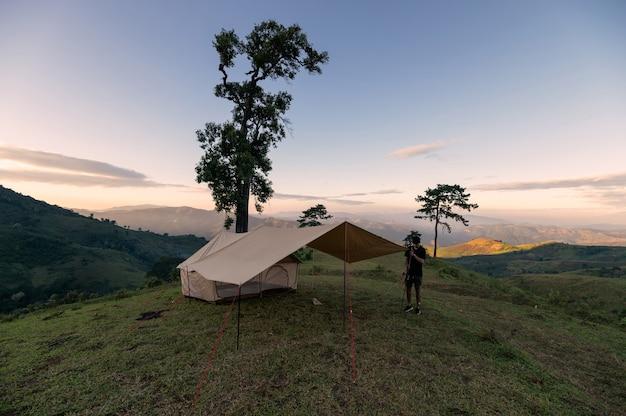 Mężczyzna rozbija namiot na zielonym wzgórzu w okolicy w godzinach wieczornych