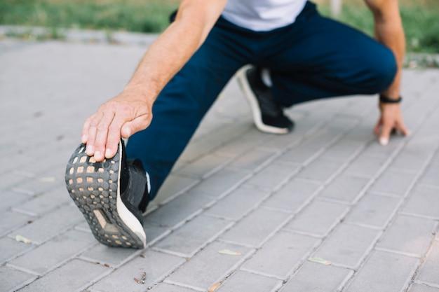 Mężczyzna rozciąga nogę na parkowej alei