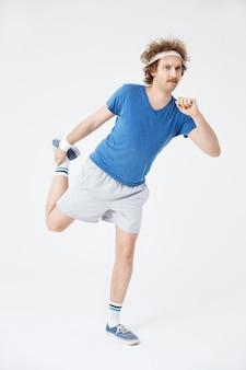 Mężczyzna rozciąga prawą nogę trzyma stopę z prawą ręką