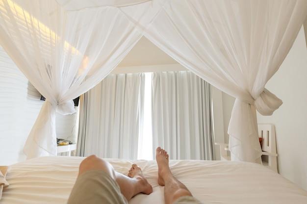 Mężczyzna rozciągający nogi w moskitierze na łóżku na wakacjach, światło słoneczne przez białą zasłonę w sypialni