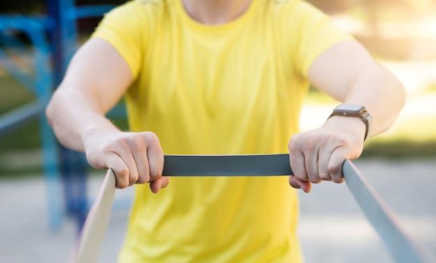 Mężczyzna rozciągający się na elastycznej gumie podczas treningu ulicznego