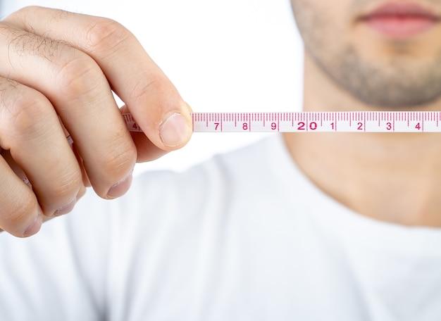 Mężczyzna rozciągający taśmę pomiarową na zdjęciu z białym tłem dla koncepcji odchudzania