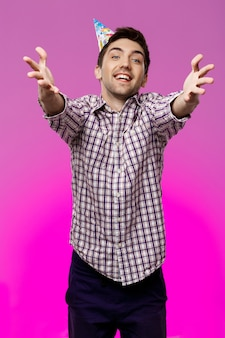 Mężczyzna rozciąganie ręce nad fioletową ścianą. przyjęcie urodzinowe.