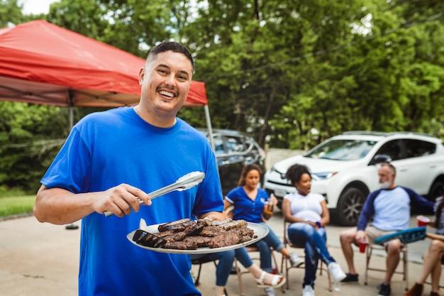 Mężczyzna rozdający hamburgery na imprezie na tylnej klapie