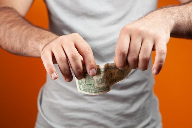 Mężczyzna rozdziera banknot na pomarańczowym tle
