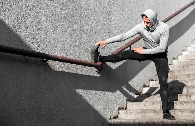 Mężczyzna rozgrzewa nogi za pomocą poręczy
