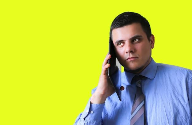 Mężczyzna rozmawia na tablecie przy uchu. komunikacja nowych technologii. na białym tle na żółtym tle.