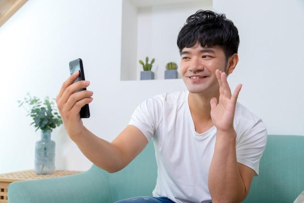 Mężczyzna rozmawia na wideokonferencji online z telefonu komórkowego w domu. porozmawiaj podczas rozmowy wideo ze znajomym lub krewnym.