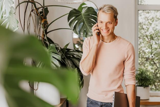 Mężczyzna rozmawia przez telefon, biznesmen z laptopem w obszarze roboczym w kawiarni eco z roślinami