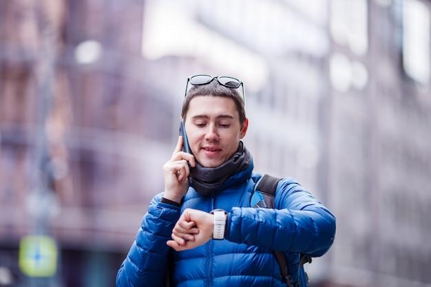 Mężczyzna rozmawia przez telefon i patrząc na smartwatch