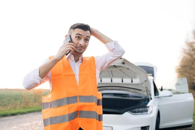 Mężczyzna rozmawia przez telefon i patrzy na silnik samochodu