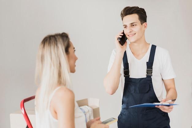 Mężczyzna rozmawia przez telefon i przytrzymanie schowka