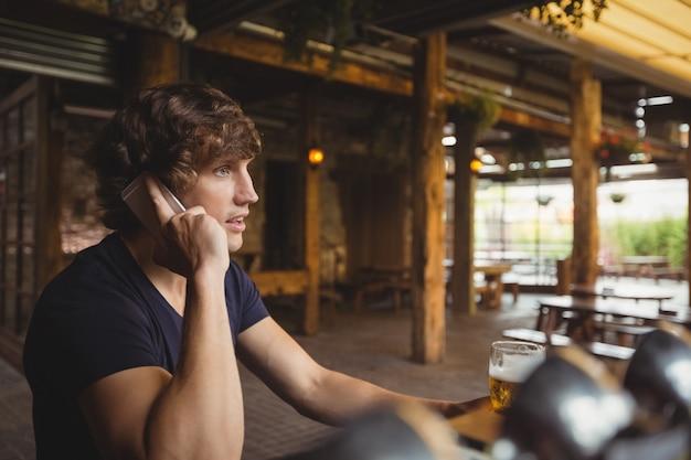Mężczyzna rozmawia przez telefon komórkowy w barze