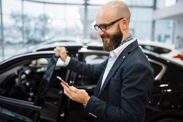 Mężczyzna rozmawia przez telefon komórkowy w pobliżu nowego samochodu w salonie samochodowym. klient w salonie samochodowym, mężczyzna kupujący transport, firma dealera samochodowego dealer